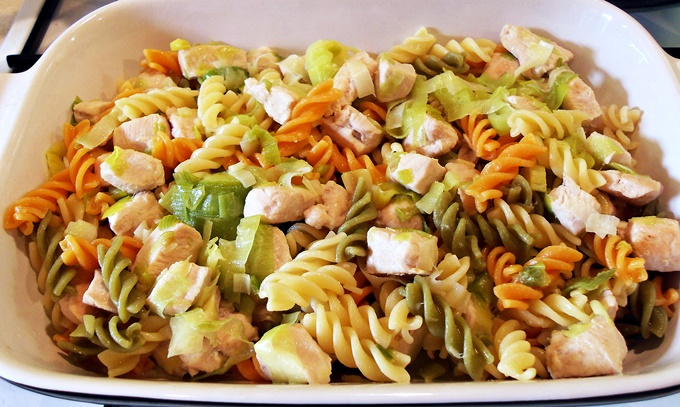 Cooked chicken, leeks and pasta in a dish.