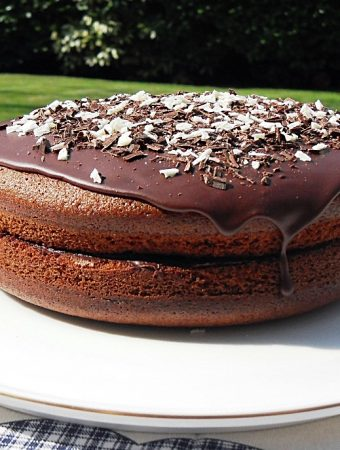 Olive Oil Chocolate Cake on a cake plate in garden.