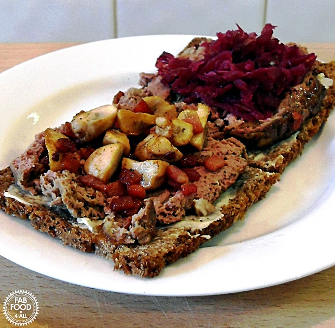 Leverpostej (Danish Liver Pate) on rye bread with fried mushrooms & bacon on 1 slice and red cabbage topping on the other.
