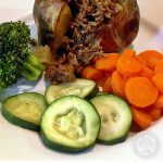 Minced Beef & Onions in a jacket potato on a plate with vegetable. Pinterest image.