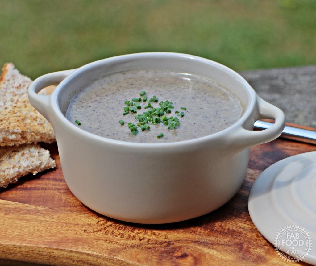 Mushroom Soup in a bowl on wooden board in garden.