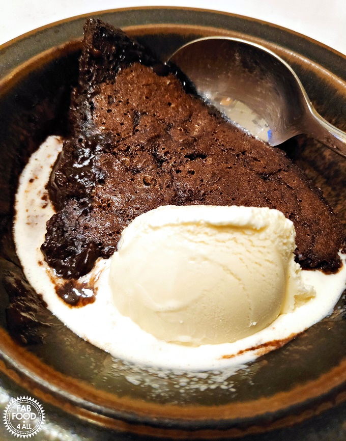 Chocolate Puddle Pudding with vanilla ice cream in a bowl.
