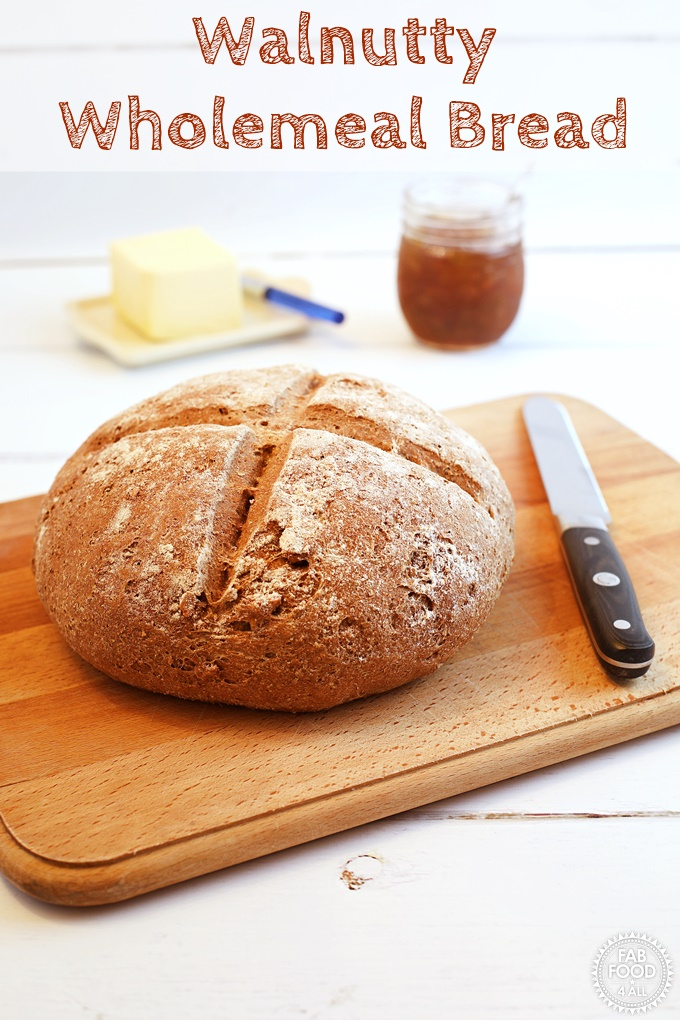 Walnutty Wholemeal Bread on a chopping board with knife with jam & butter in background.