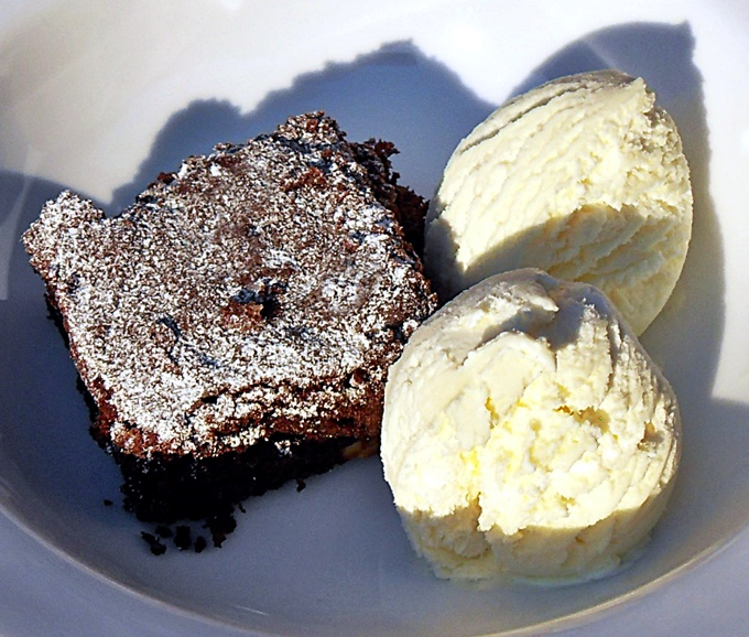 Specunana Brownies with ice cream in a bowl.