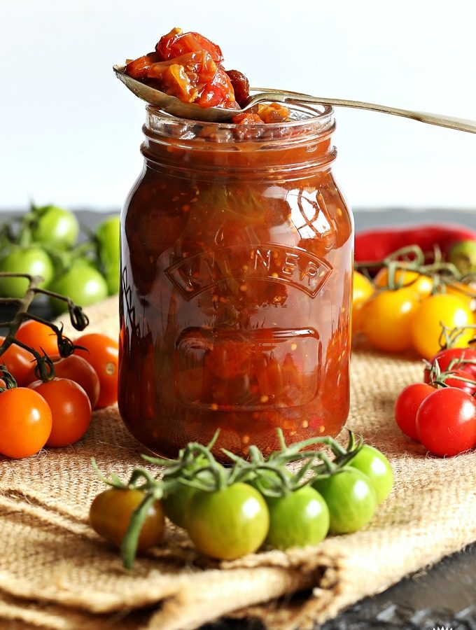 Mixed Tomato Chutney in a jar surrounded by cherry tomatoes in various colours.