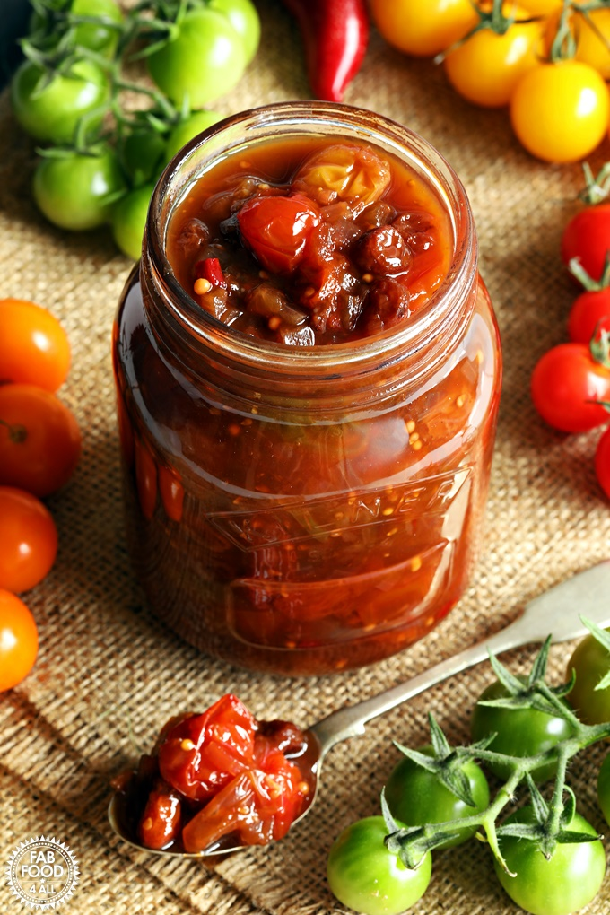 A jar of Mixed Tomato Chutney surrounded by green, red, yellow & orange cherry tomatoes.