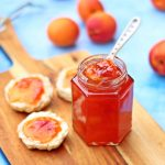 Jar of Peach & Apricot Jam with a spoon and scones on a wooden board surrounded by peaches, nectarines and apricots.