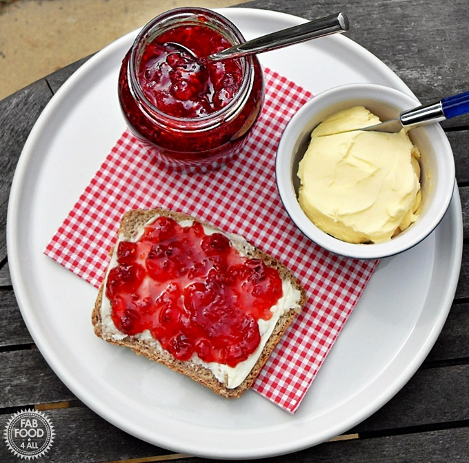 Aerial view of Strawberry, Raspberry & Redcurrant Jam on bread and butter with jar or jam and bowl of clotted cream.