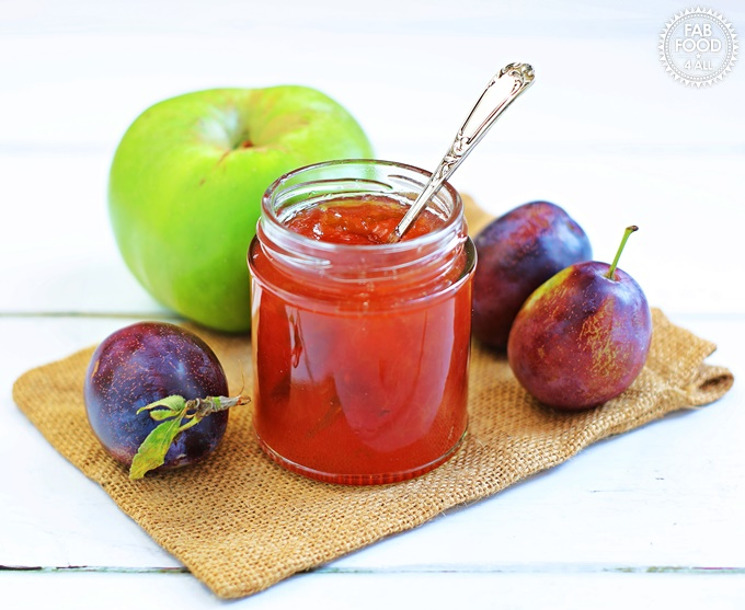 Plum & Apple Jam in open jar with teaspoon flanked by Marjorie plums & a Bramley apple.
