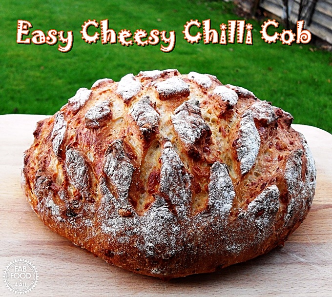 Easy Cheesy Chilli Cob on a wooden board, side view.