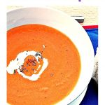 Cream of Tomato & Basil Soup in bowl swirled with cream. Pinterest image.