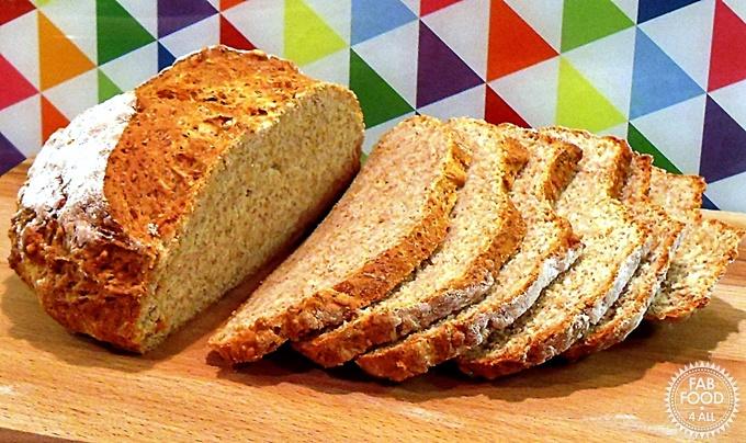 Sliced Emmental Soda Bread Loaf on a wooden board.