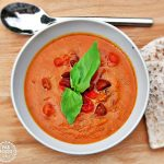 Roasted Tomato, Red Pepper & Chorizo Soup with basil leaf garnish.