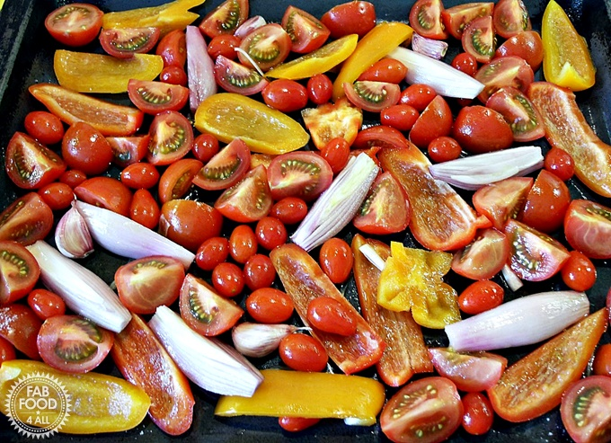 Tomatoes, peppers and onions on a roasting tray.