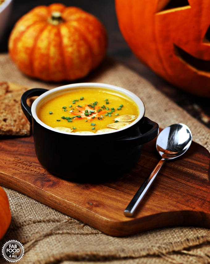 Curried Pumpkin Soup in a bowl on a board in front of pumpkins.