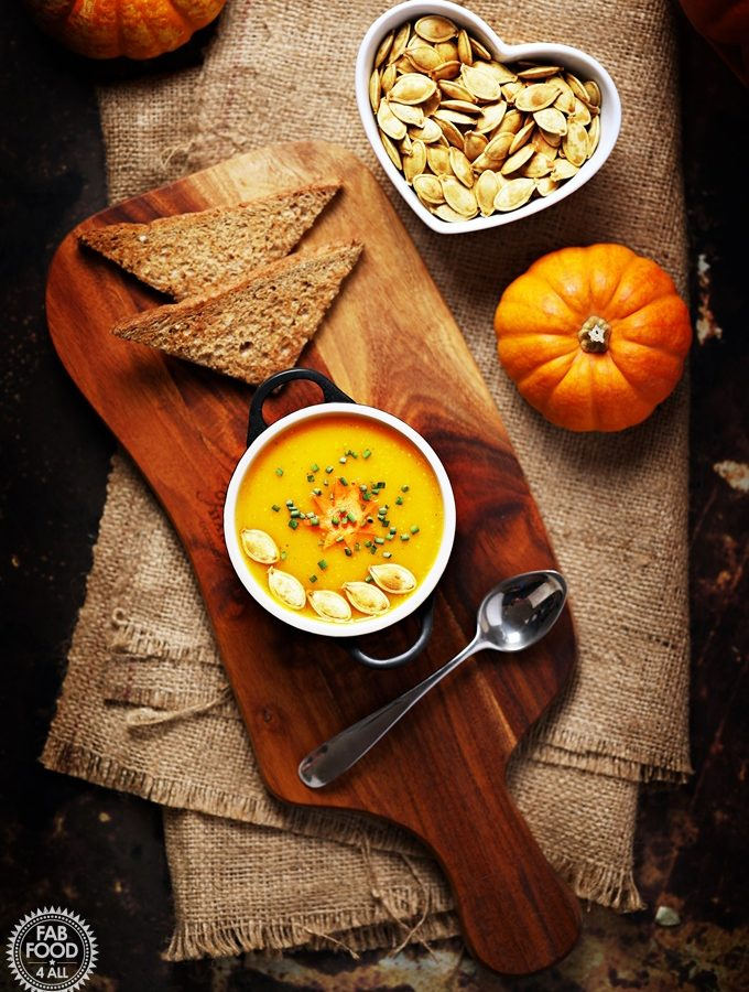 Curried Pumpkin Soup on a board with toast and toasted pumpkin seeds in a bowl.