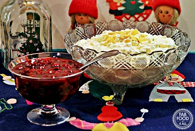 Risalamande (Danish Rice Pudding) and cherry sauce in glass serving dishes. on a traditional Danish table cloth.
