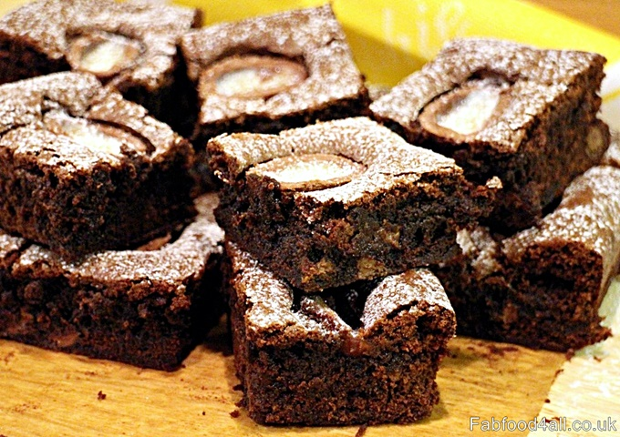 Creme Egg Brownies stacked up on a wooden board with baking parchment.