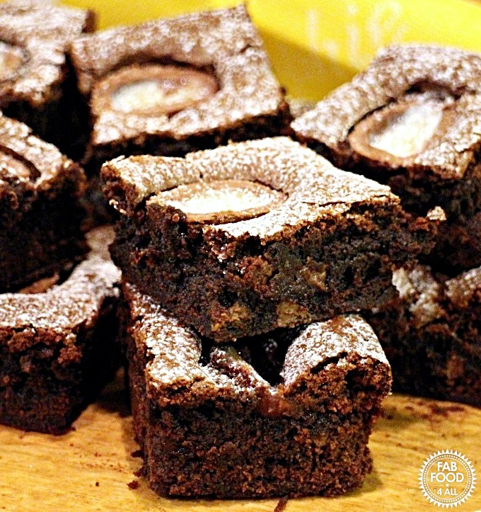 Close up of Creme Egg Chocolate Brownies stacked up on a wooden board.
