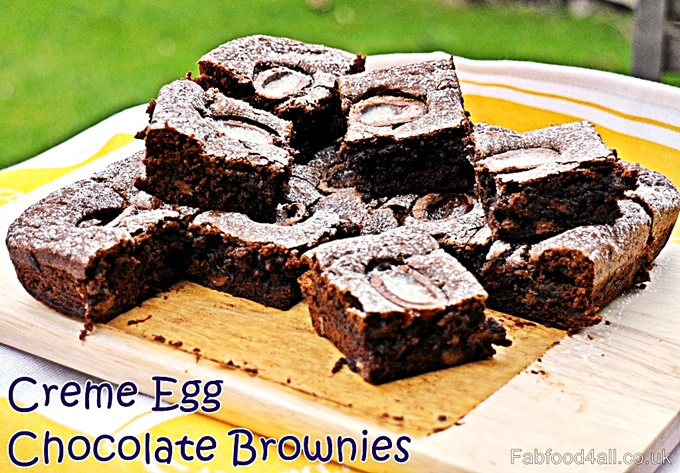 Creme Egg Brownies stacked up on a wooden board.