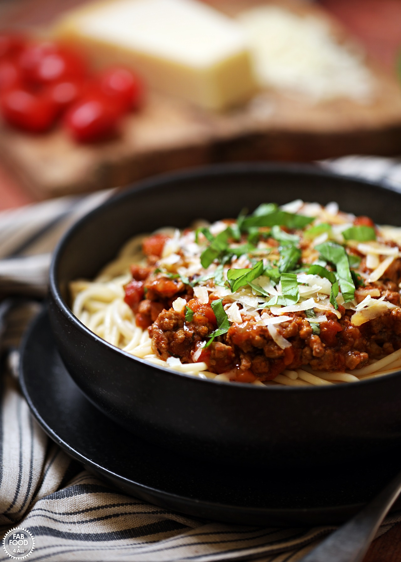 Turkey Bolognese in a bowl with spaghetti & grated parmesan with tomatoes and Parmesan cheese in background.