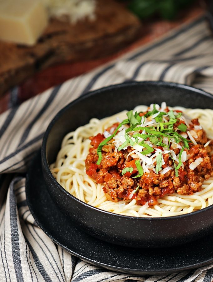Turkey Bolognese in a bowl with spaghetti & grated Parmesan in background.