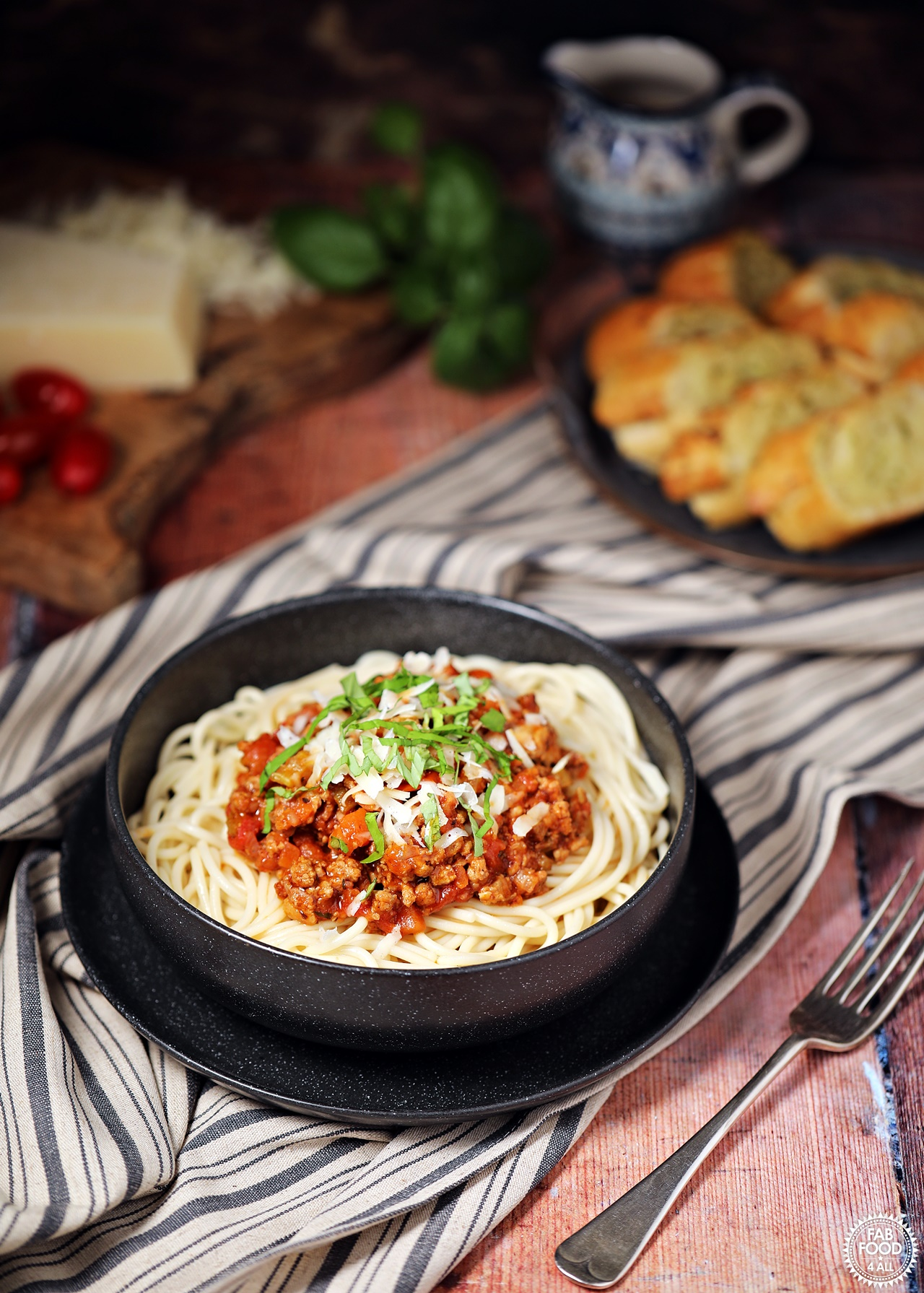 Turkey Bolognese in a bowl with spaghetti & grated parmesan with garlic bread & tomatoes in background.