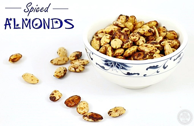 Spiced Almonds in a bowl with a few scattered around.