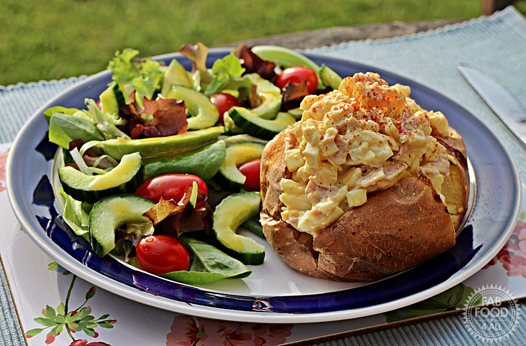 Curried Egg Mayonnaise with Ham & Sweetcorn Jacket Potato on a dinner plate with salad.