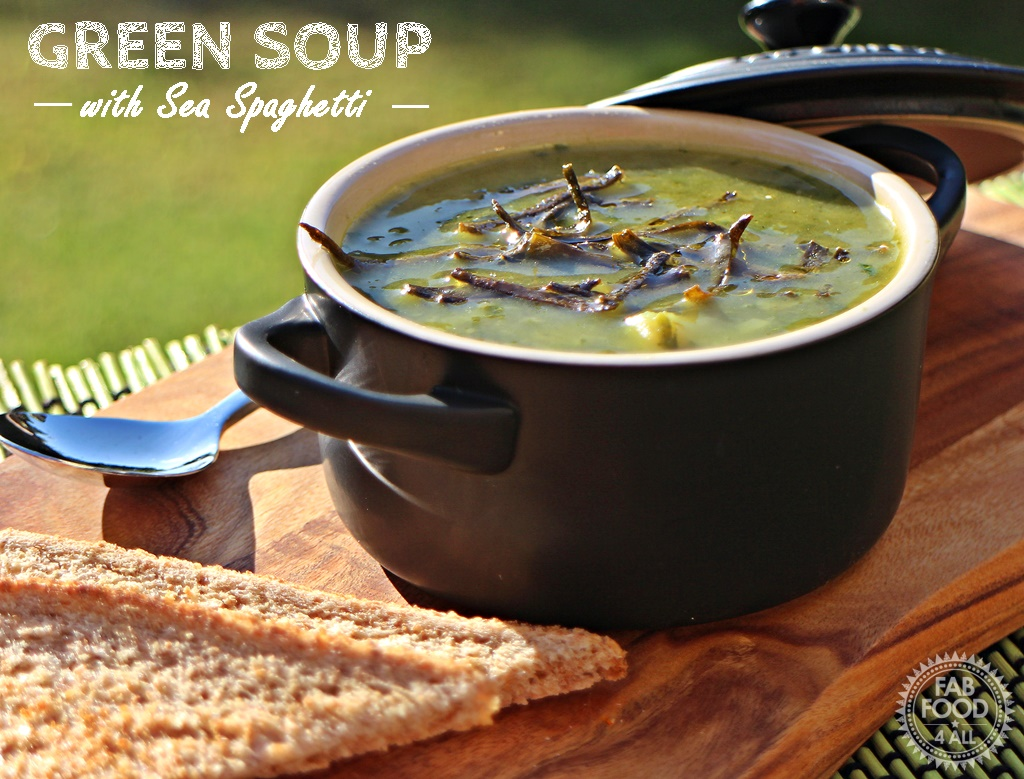 Green Soup with Sea Spaghetti on a board with spoon & toast.