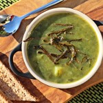 Green Soup with Sea Spaghetti on a board with spoon & toast. - aerial view