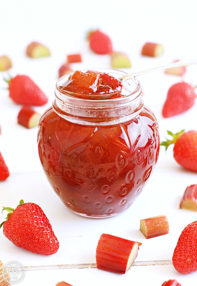 Pot of Rhubarb & Strawberry Jam with teaspoon surrounded by strawberries & slices of rhubarb.