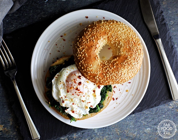 Quick Poached Egg & Garlic Spinach Bagel served on a white plate on a slate.