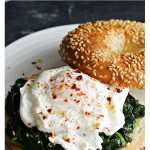 Poached Egg & Garlic Spinach Bagel served on a white plate on a slate.