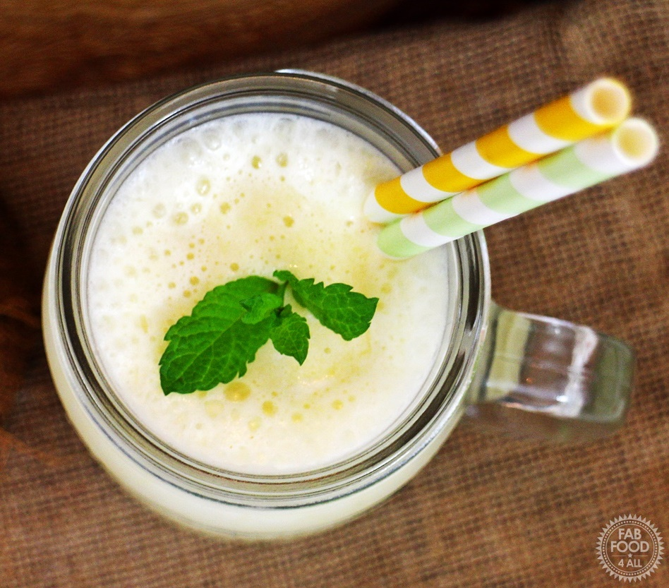 Pineapple & Coconut Smoothie in glass mug with sprig of mint & 2 straws. Aerial view.