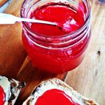 Jar of Easy Seedless Raspberry Jam with currant bun.