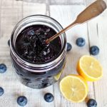 Simple Blueberry Jam in a jar with cut lemon & blueberries surrounding.