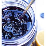 Close up of Blueberry Jam in a jar with a cut lemon. Pinterest image.