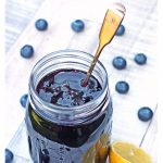 Simple Blueberry Jam in a jar with a cut lemon. Pinterest image.