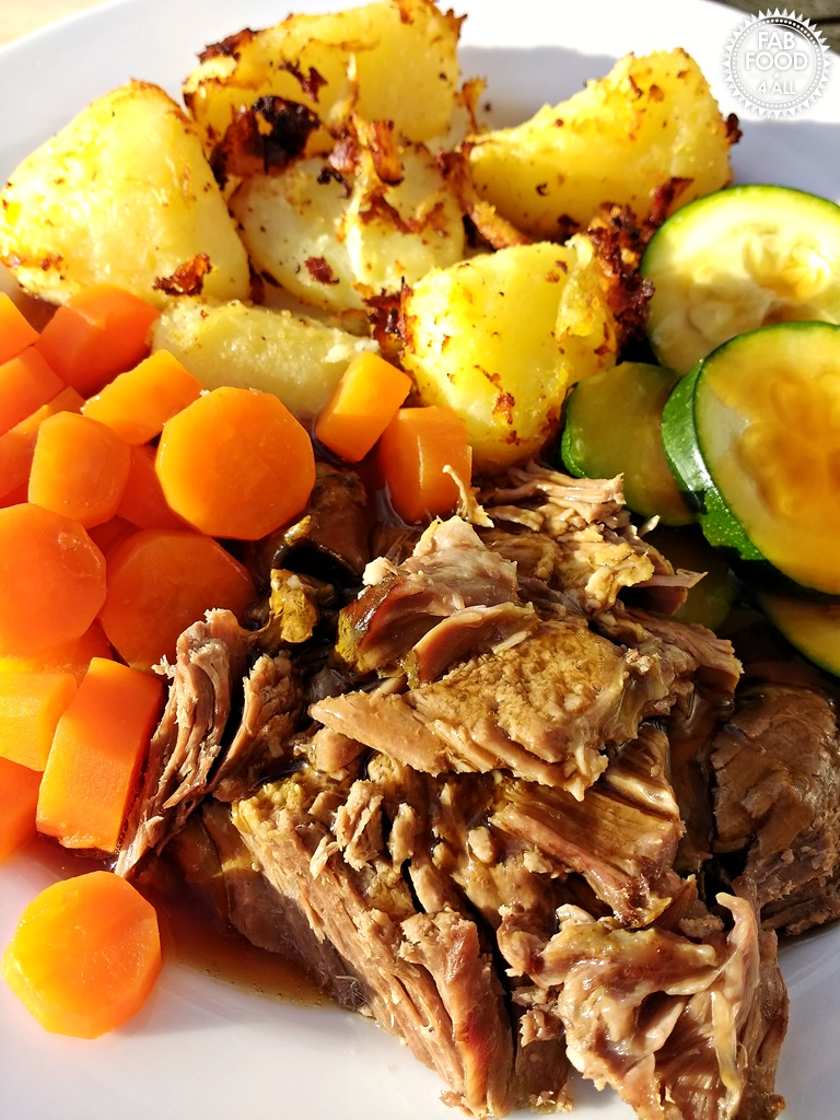 2 Ingredient Slow Cooker Roast Lamb served with roast potatoes, carrots & courgettes.