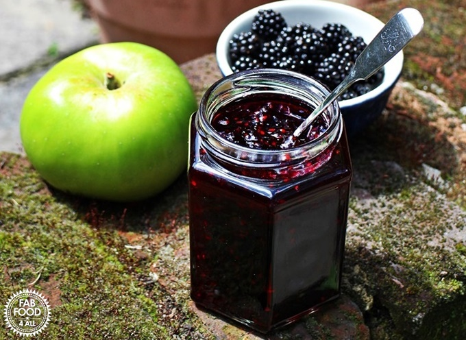 Blackberry & Apple Jam in a jar with apple & blackberries in background.