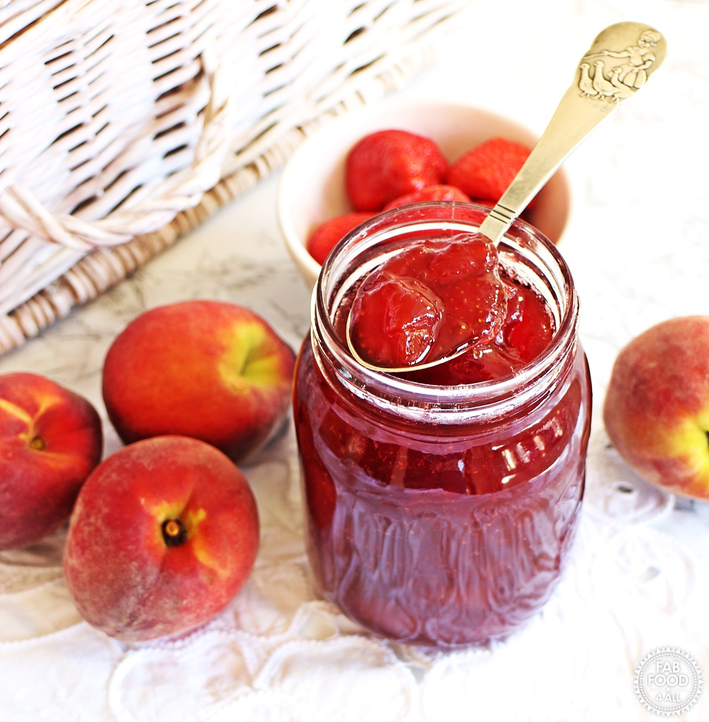 Jar of Strawberry & Peach Jam with teaspoon & fruits in background.