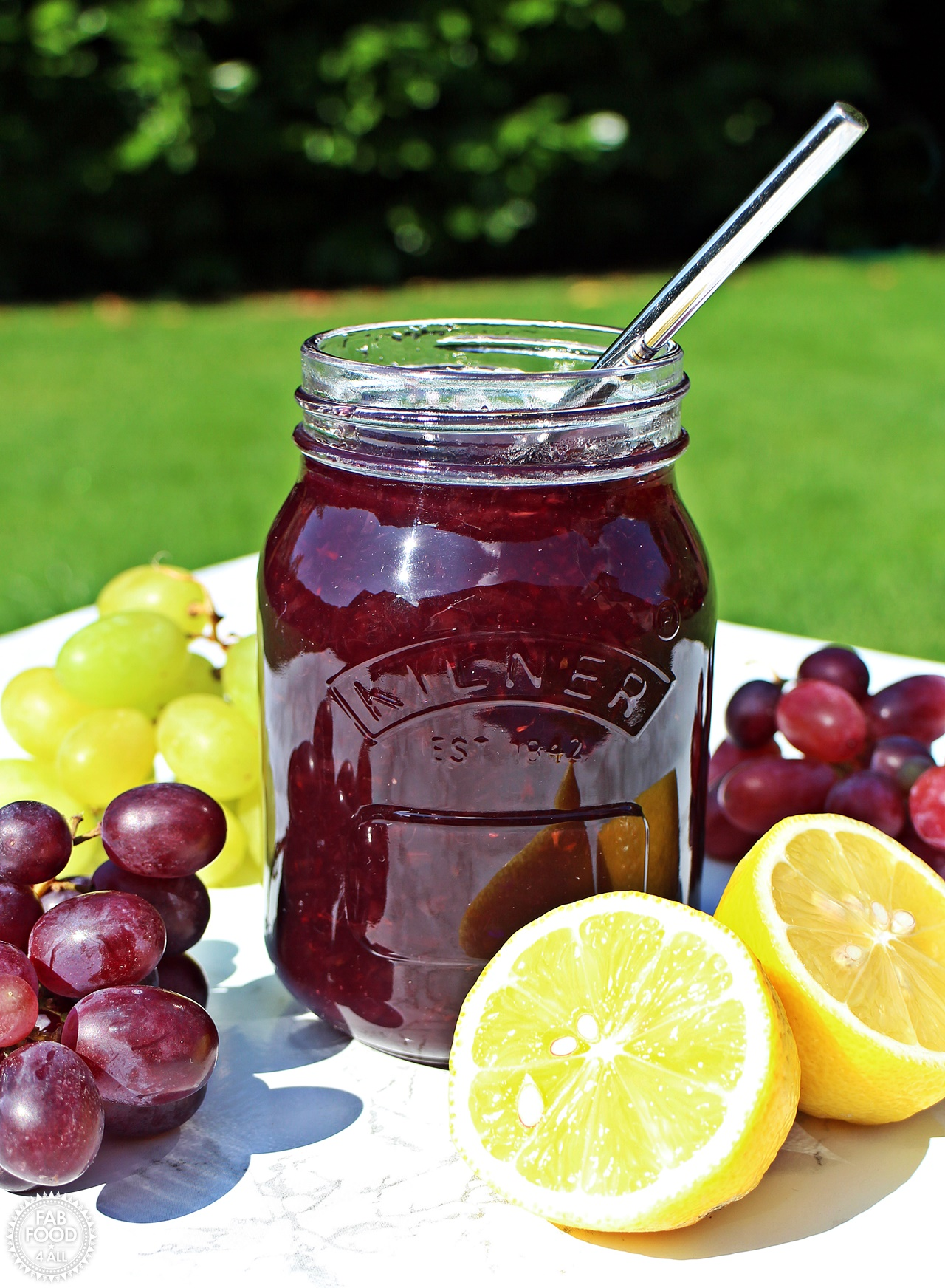 Easy Grape Jam with grapes & a cut lemon.