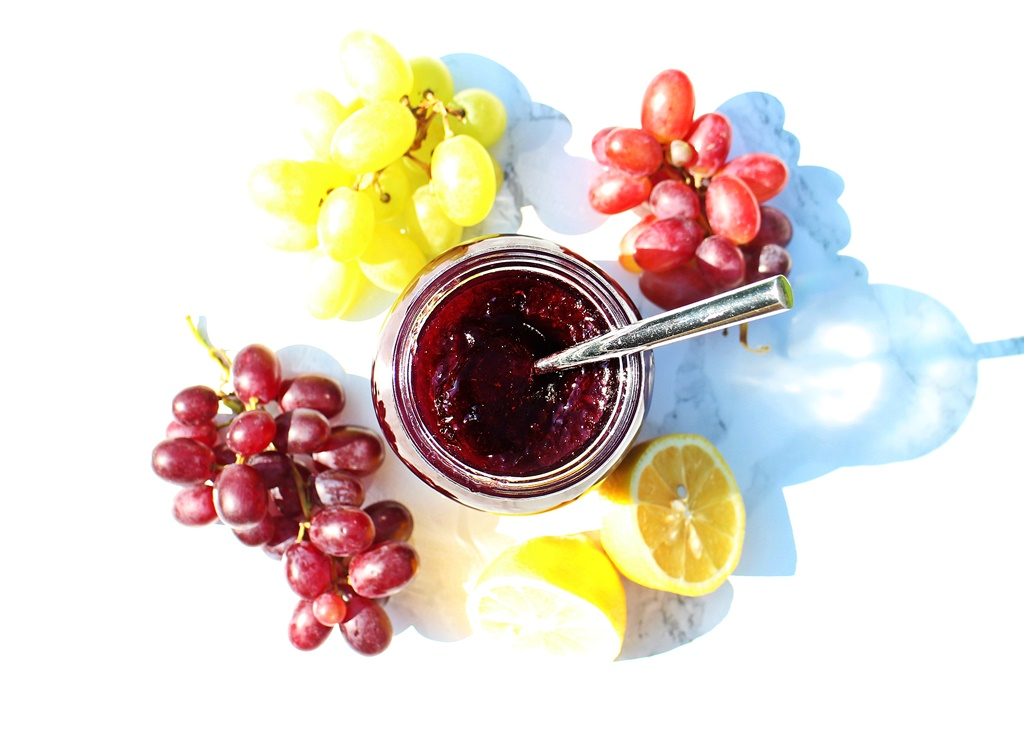 Aerial view of opened jar of Easy Grape Jam with teaspoon in jam surrounded by grapes.