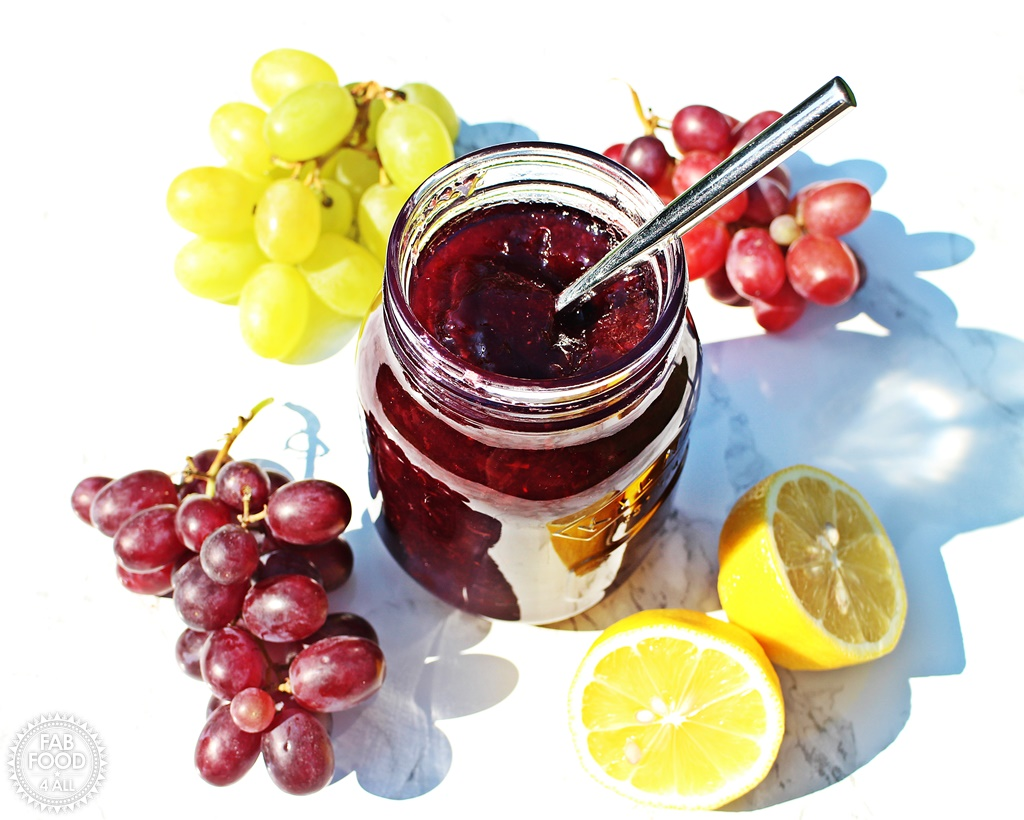 Easy Grape Jam in jar with teaspoon in, surrounded by grapes and a cut lemon.