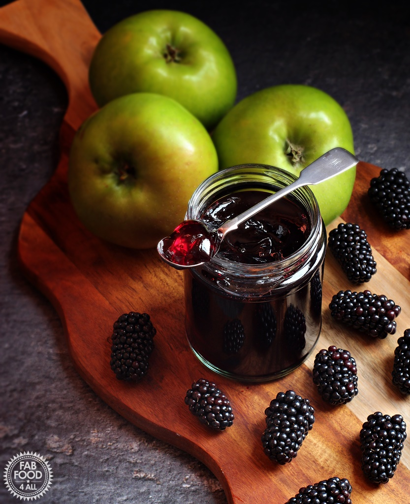 Jar of Easy Blackberry & Apple Jelly on a board with Bramley apples and blackberries.