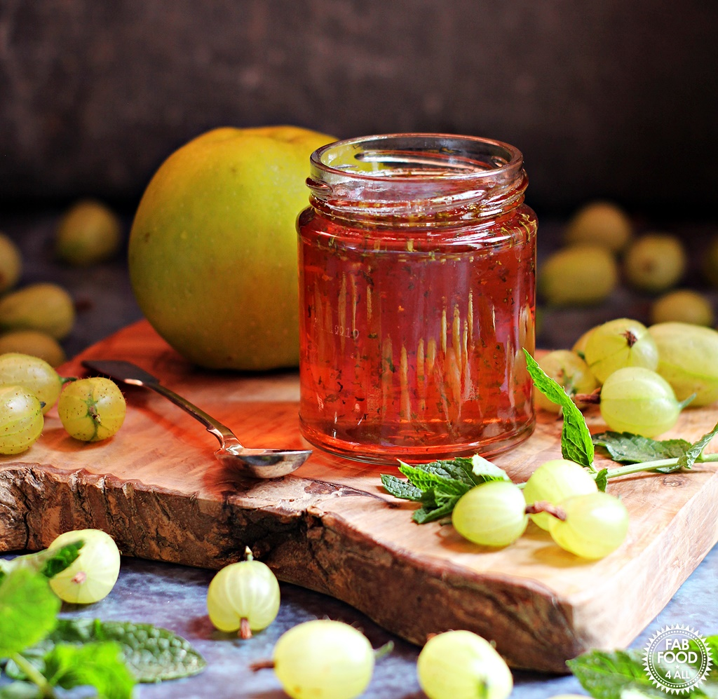 Gooseberry, Apple & Mint Jelly on a board surrounded by gooseberries, Bramley apple, and mint leaves.