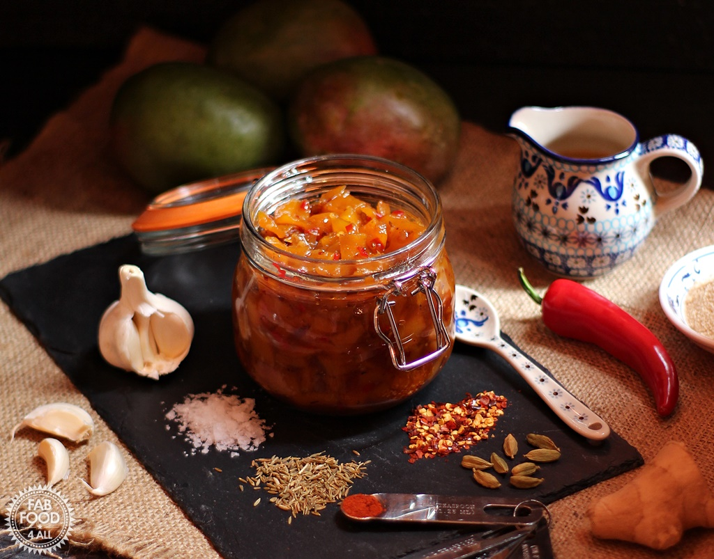 Easy Spicy Mango Chutney with ginger root, garlic, crushed chillies, cardamon, cumin seeds, paprika, salt, red chilli, cider vinegar and soft light brown sugar on a slate.