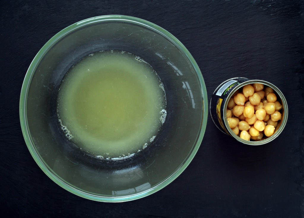 Aquafaba (chickpea water) in a glass bowl and can of chickpeas