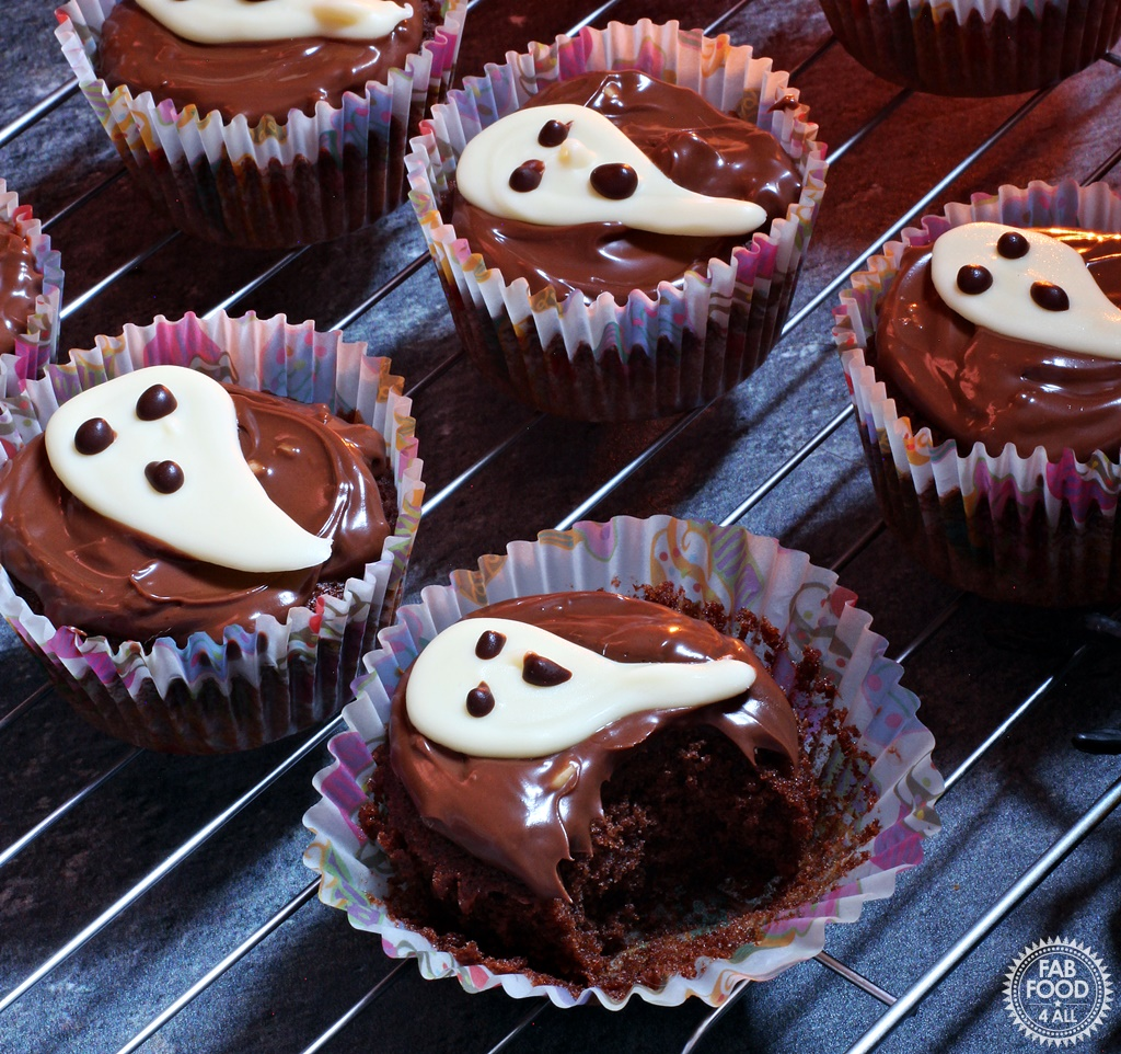 Easy Halloween Ghost Cupcakes - delicious chocolate & coffee flavoured sponge topped with chocolate spread & a handmade white chocolate ghost. Teeth marks in the cake in the forefront!